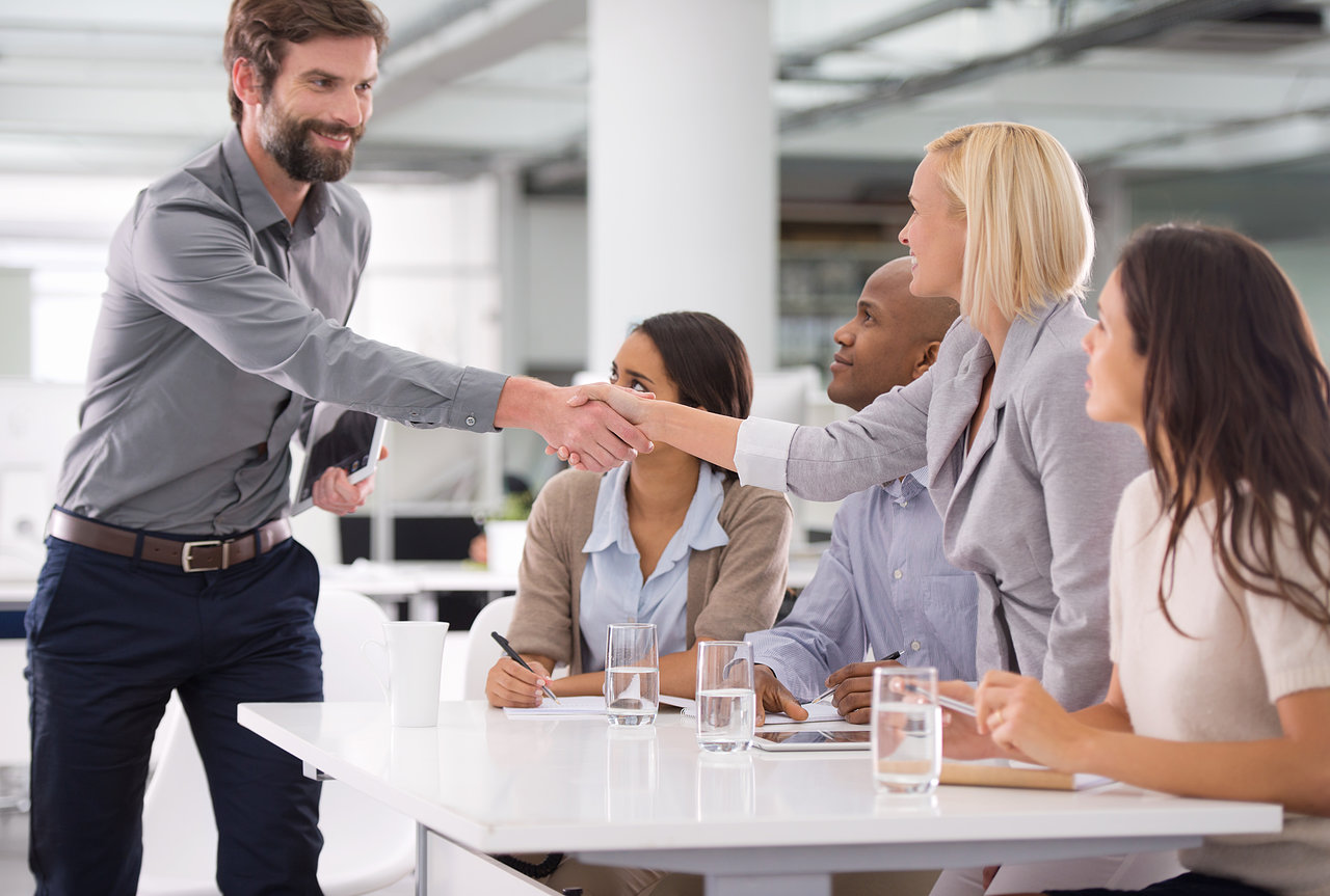 Shot of a businessman shaking the hands of his colleagues sitting on a panel